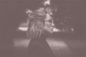 blonde woman with a half top bun in a dark setting with a pink overlay