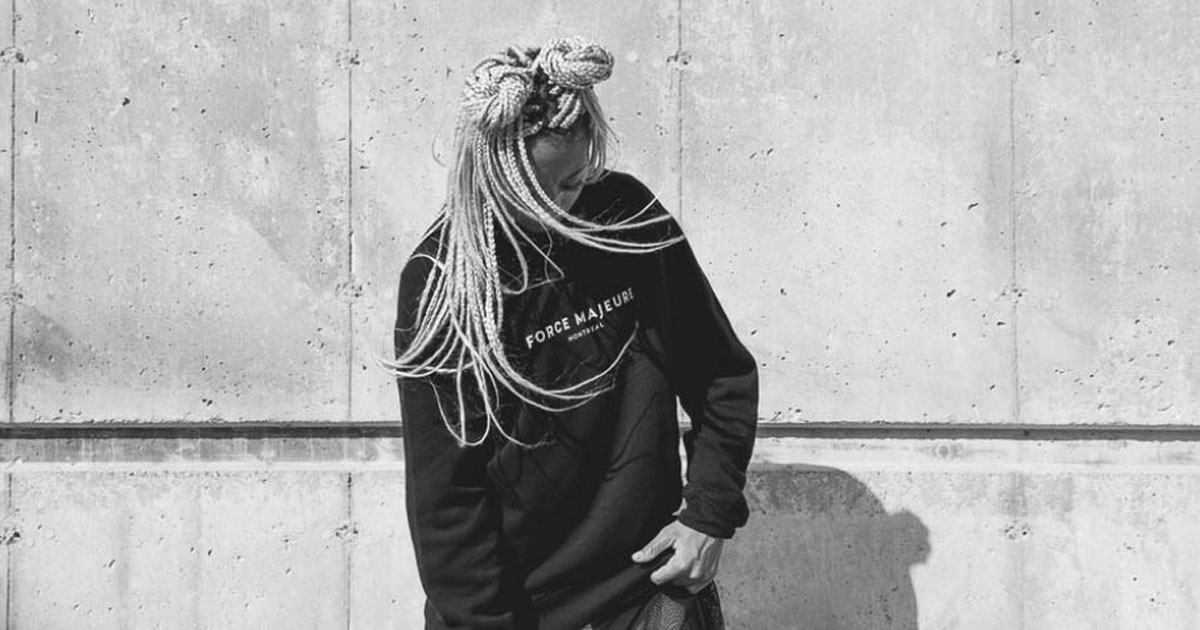 woman of color with long blonde braids in front of a concrete wall