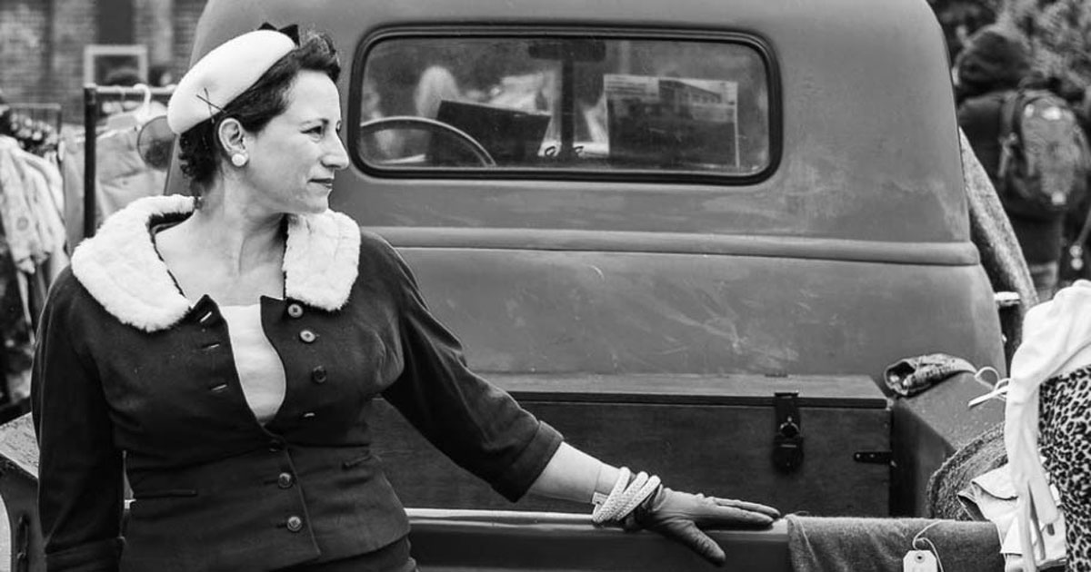mature woman in a hat and jacket behind an old pickup truck