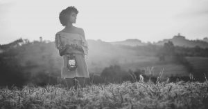 woman of color holding a lantern in a hilly field of grain