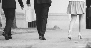 feminine person wearing a skirt and heals among people in suits