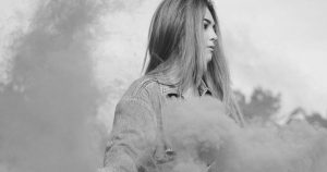 woman of color in smoke looking off camera