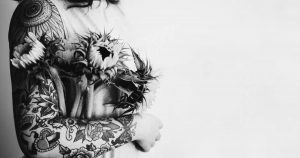 woman with tattoos holding sunflowers