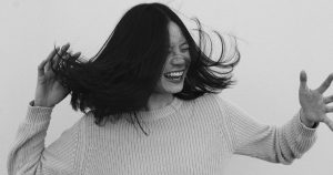 woman of asian decent shaking her hair playfully