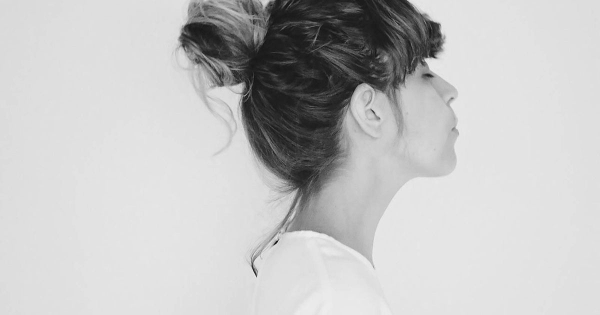 photo of a woman with a bun in a white shirt