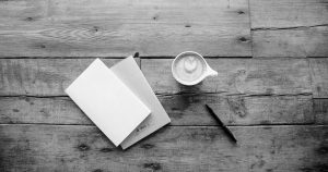 overhead photos of a latte, notebooks and a pen