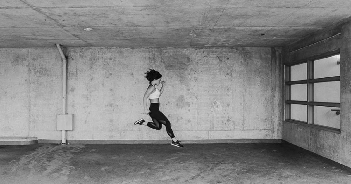 woman leaping in a concrete space in exercise clothes