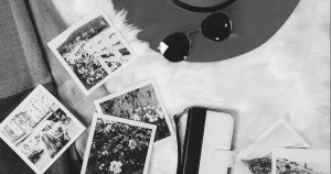 instant photos, sunglasses, brimmed hat and cell phone