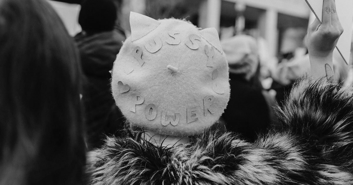 """back of a woman in a fur coat at a protest with a hat that says """"pussy power"""""""