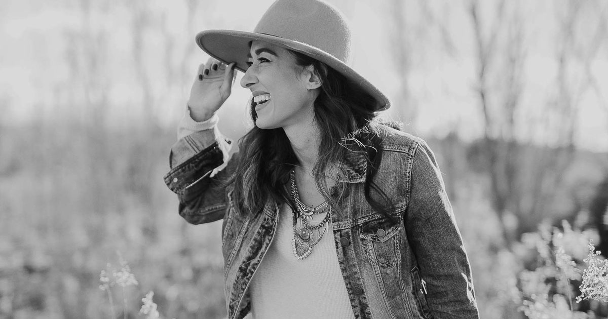 stylish woman in a hat out in nature