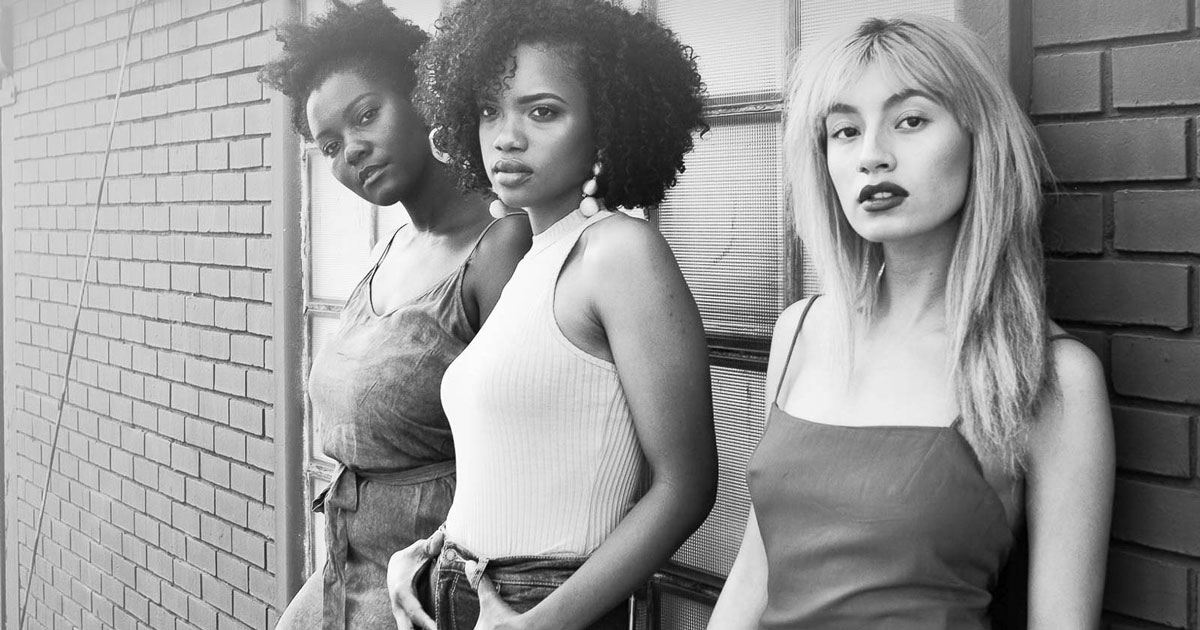 black and white image, 3 confident women of color standing by a brick wall