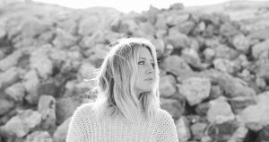 blond woman in a sweater in front of some rocks