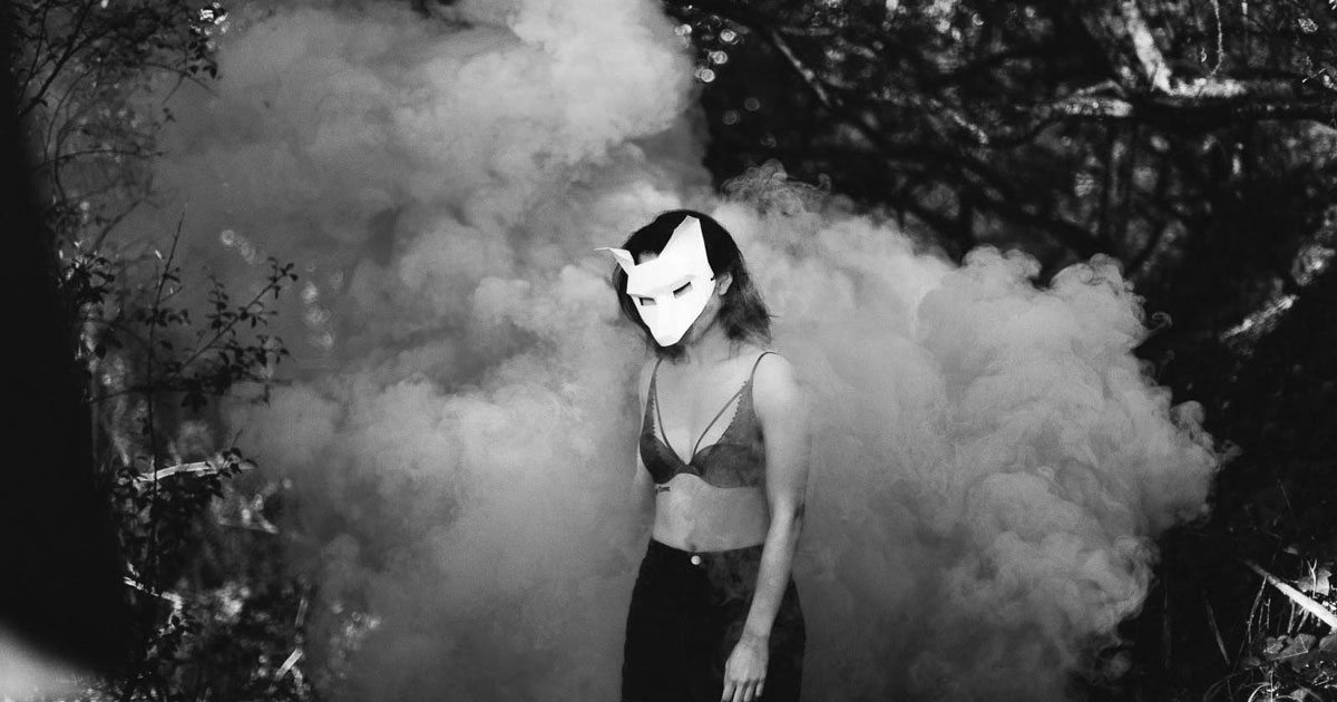 woman with a mask in the forest and smoke