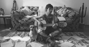 woman playing guitar with a dog and cacti