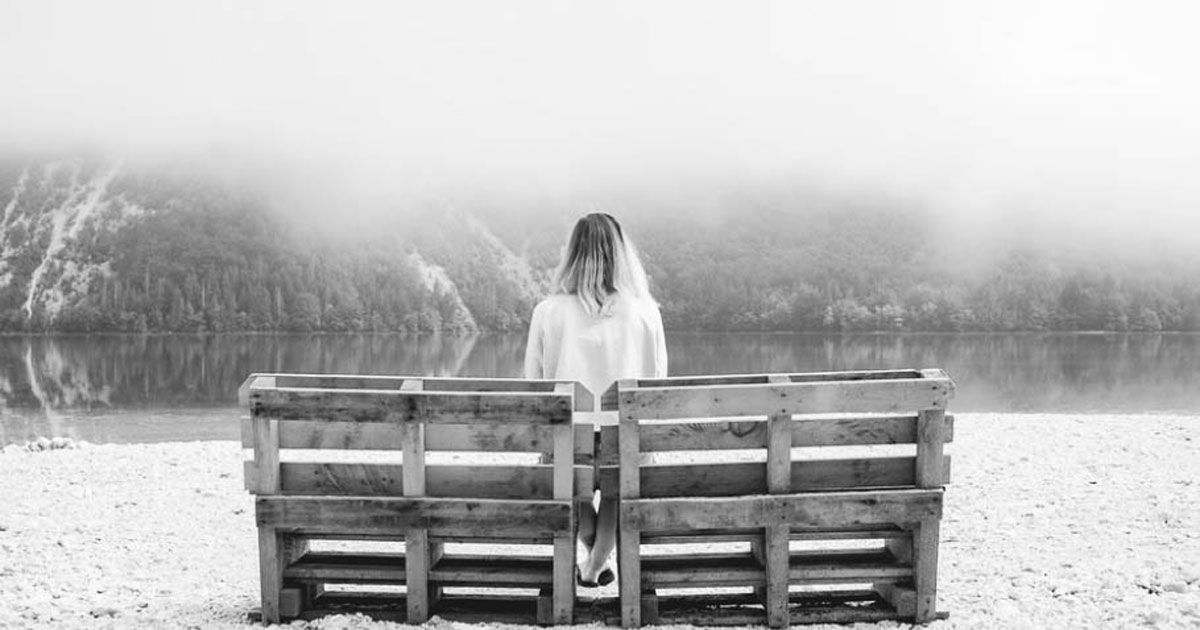 back of a woman sitting on a bench in front of a lake potentially representing anger