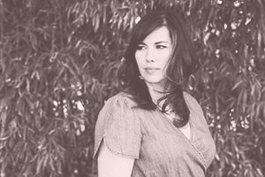 black and white photo of Natalia Amari in an outdoor scene with a pink overlay