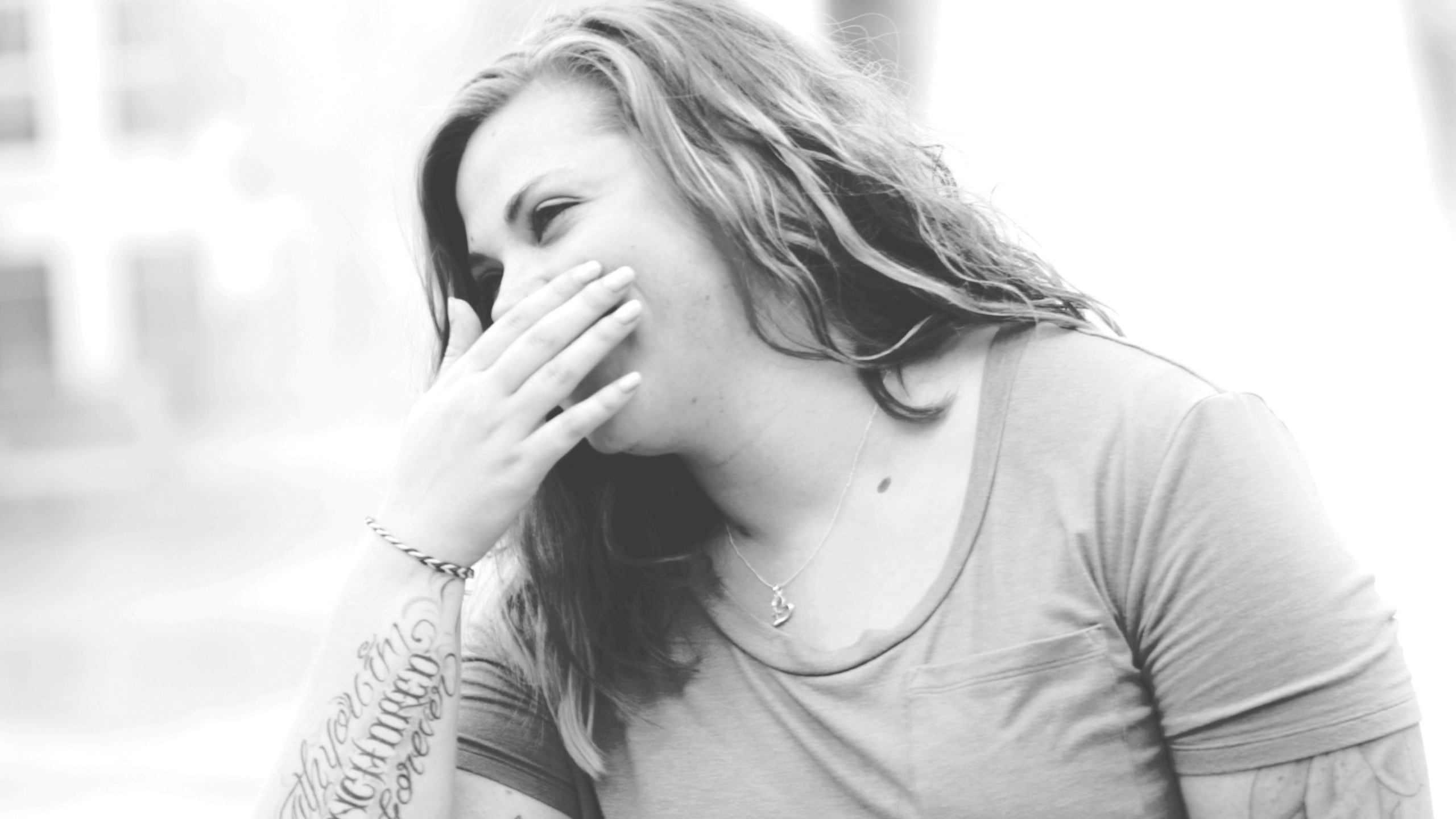 black and white image of a woman with tattoos, covering her mouth with her hand as she laughs