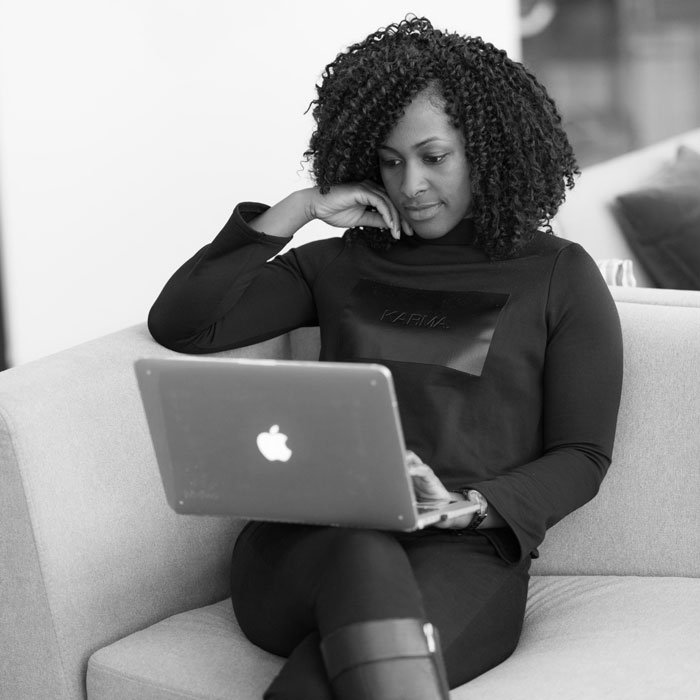 Black and white photo of a woman on a laptop