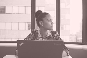 woman of color with a top bun with a laptop and a pink overlay