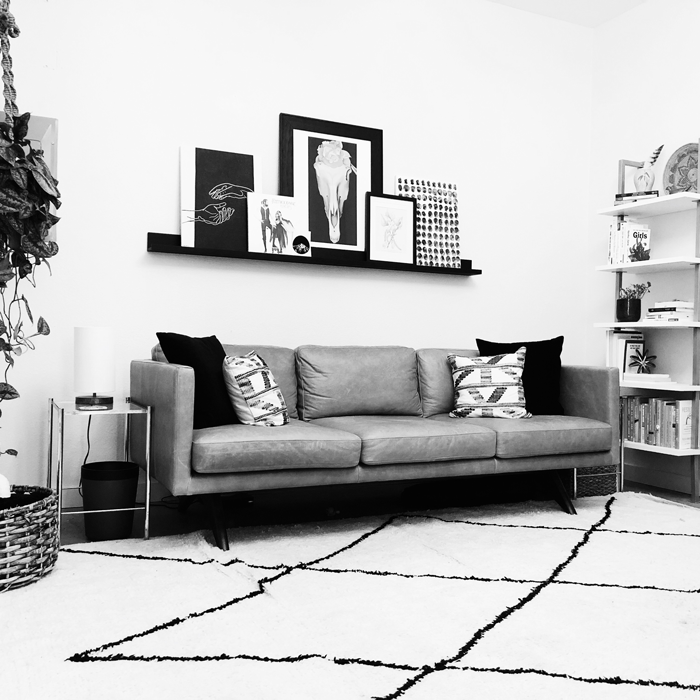 black and white image of an office with a couch with black and white throw pillows, a black and white rug on the floor, black and white shelves on the walls