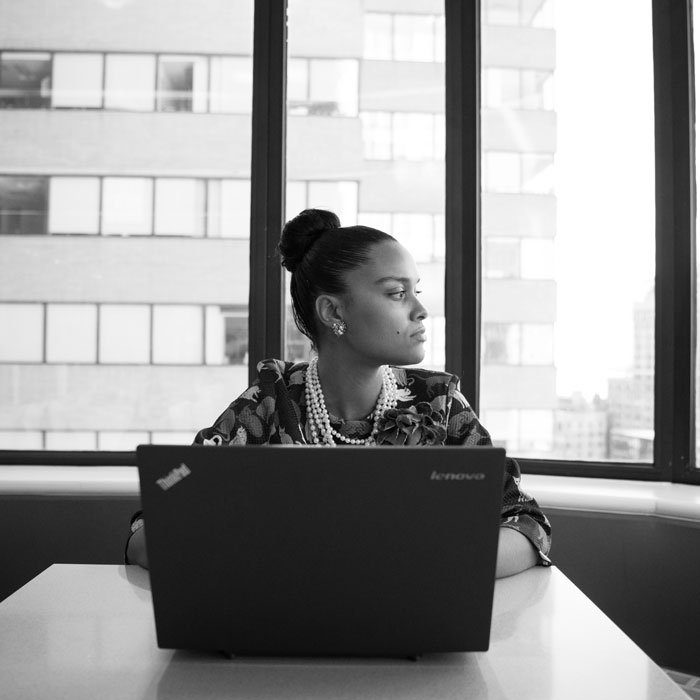 black and white image of a woman with her hair in her bun, working at a laptop