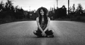 black and white photo of woman of color sitting in the middle of the road for blog post about fall equinox