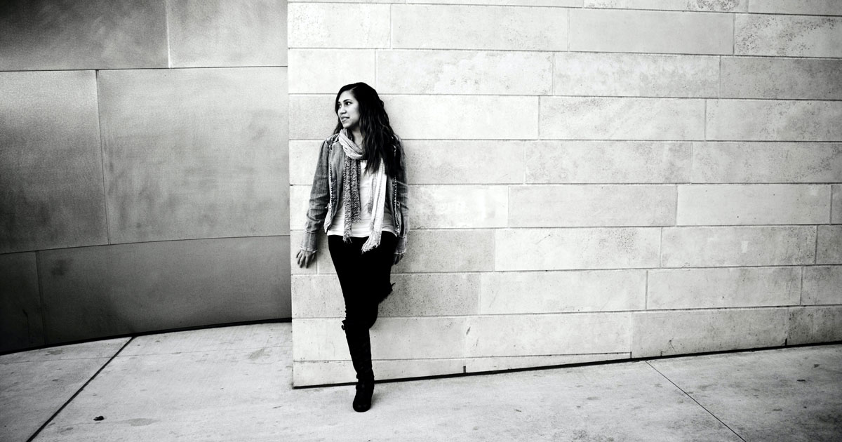 black and white image of ethnic woman standing against a light colored brick wall for blog post on intergenerational trauma by natalia amari of rebel in bloom