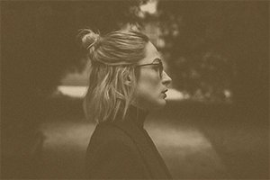 blonde woman with a half top bun in a dark setting with a gold overlay