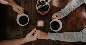image of two people holding hands across the table, coffee mugs in each of their other hands